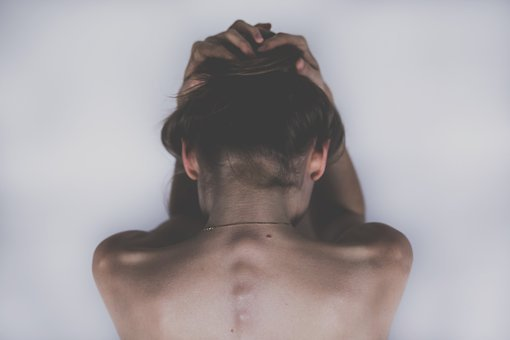 topless woman holding head down with both hands